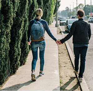 Man and Woman holding hands walking down a street, happy with their financial situation
